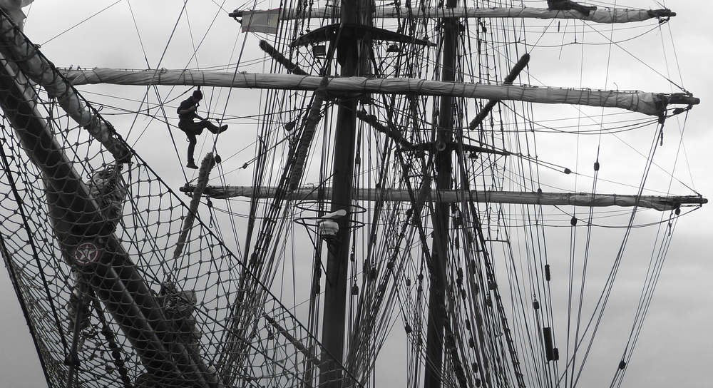 sailors working aloft in the rigging of a traditional tallship