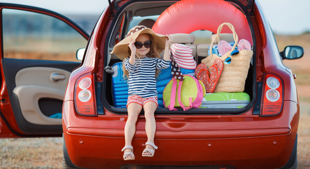 Girl sitting on back bumper of car with beach gear in trunk