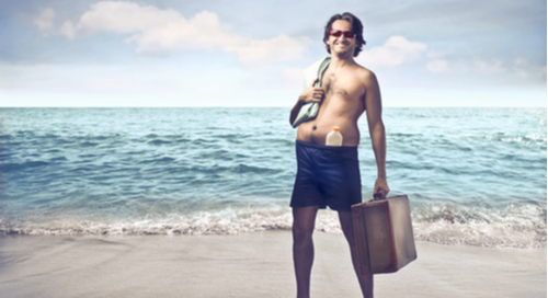 A smiling man holding a briefcase on a beach