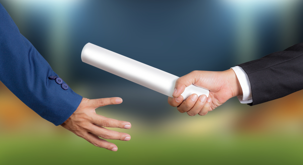 One hand holding a rolled document handing to another hand like a relay