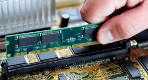 Picture of someone installing memory on a computer motherboard