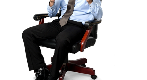 Businessman in chair clenching first