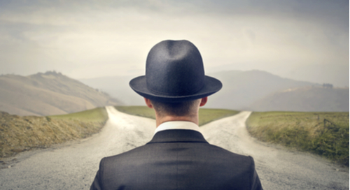 Man in suit and hat looking at a fork in a road leading left and right