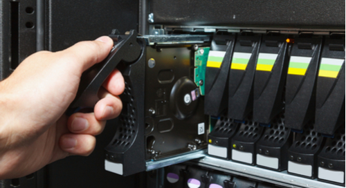 Hand replacing memory storage unit on computer