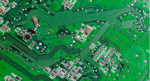 Close up picture of power and signal routing on a green PCB