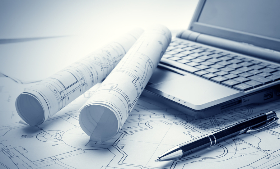 A pen and a laptop on top of blueprints with two rolled schematics