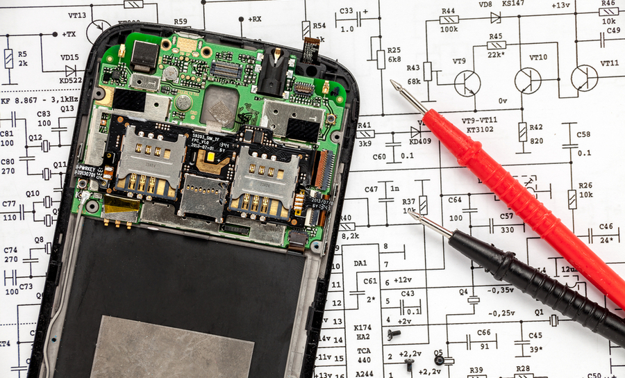 PCB in a smartphone over an electronic schematic