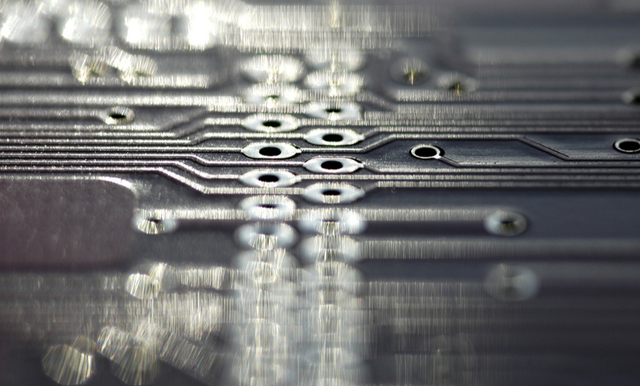 Long line of drill holes on grey PCB