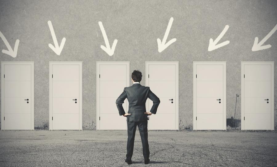 Businessman standing in front of doors