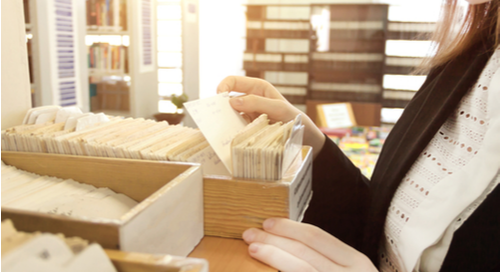 Woman searching through a library card catalog