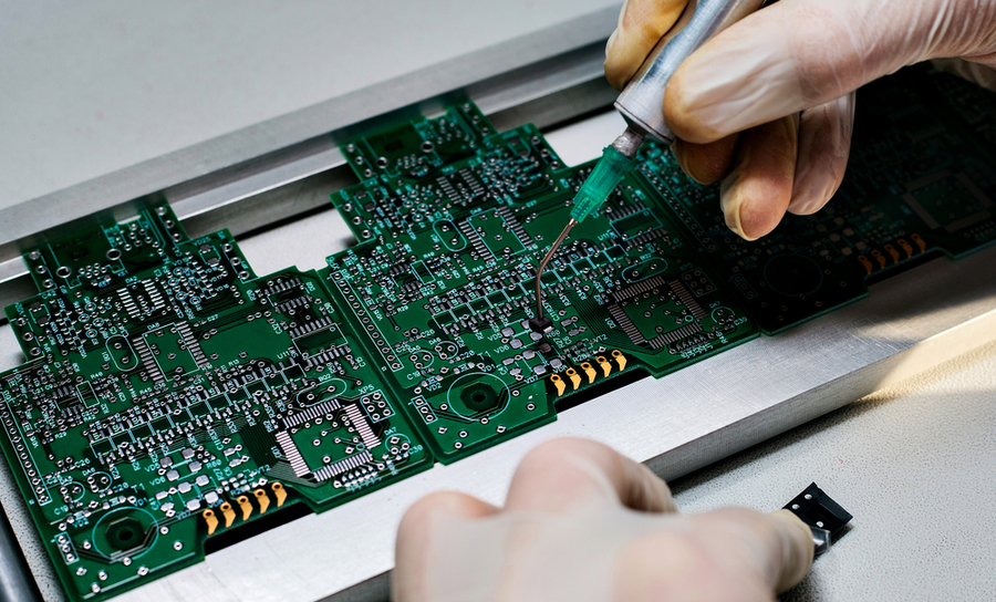 Worker assembling components on a green PCB
