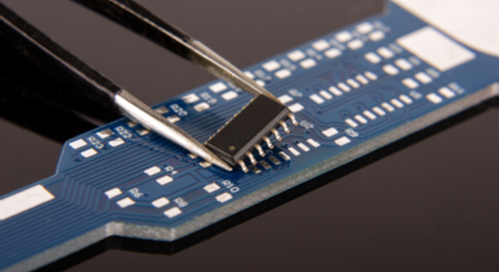 Surface mount IC in tweezers over a blue PCB