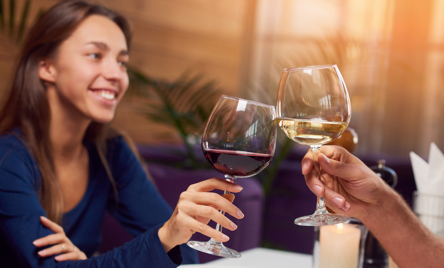 A smiling girl drinking red wine toasts a friend drinking white wine