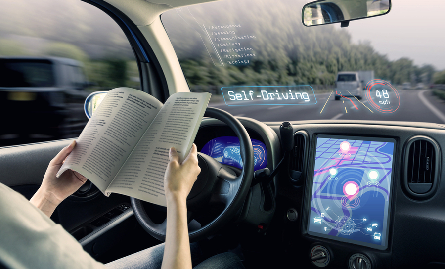 Woman in a self-driving car reading a book