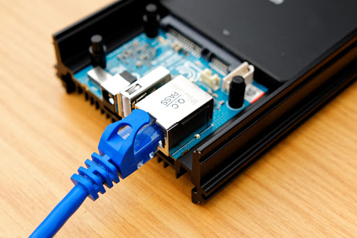 An ethernet cable connected to an ODroid HC1 in its casing and connected to a Samsung EVO SSD