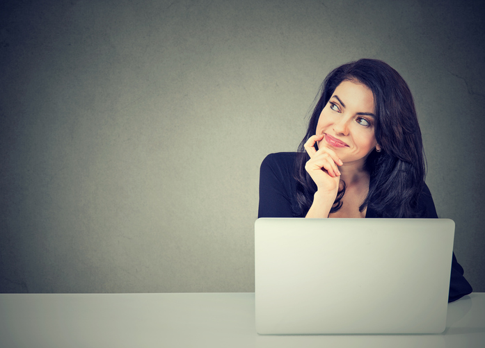 Woman at laptop with head in her hand