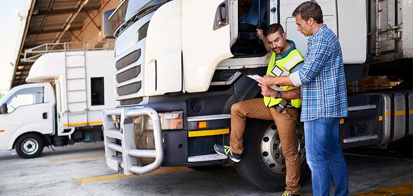picture of two men looking over order before driver leaves for a delivery.