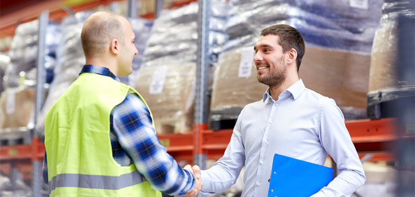men shaking hands in warehouse, revolutionizing customer experience.