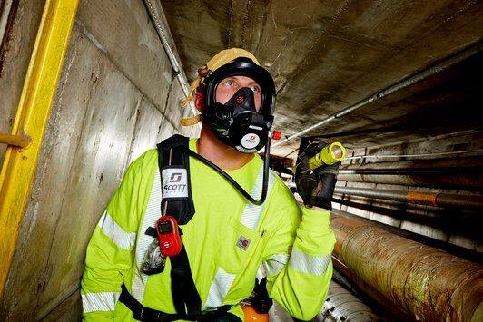 Man in tunnel with flashlight and respiratory gear.