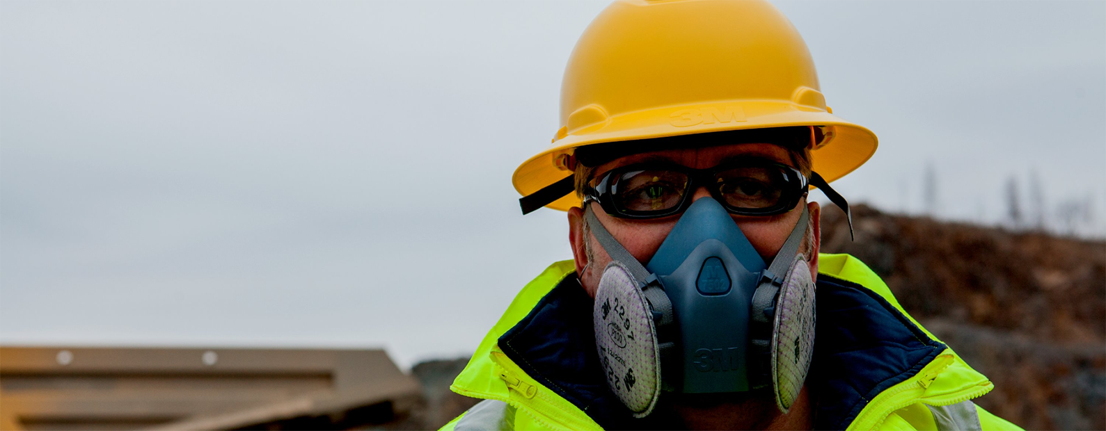 Man wearing hard hat, respirator, and eye protection.