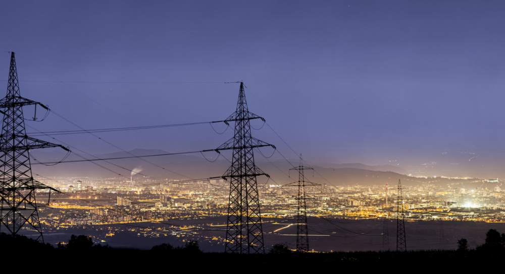 Überlandleitungen vor den Lichtern einer Stadt.