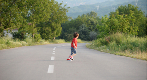 Child running across a road