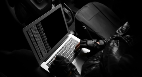 Thief hacking car with laptop