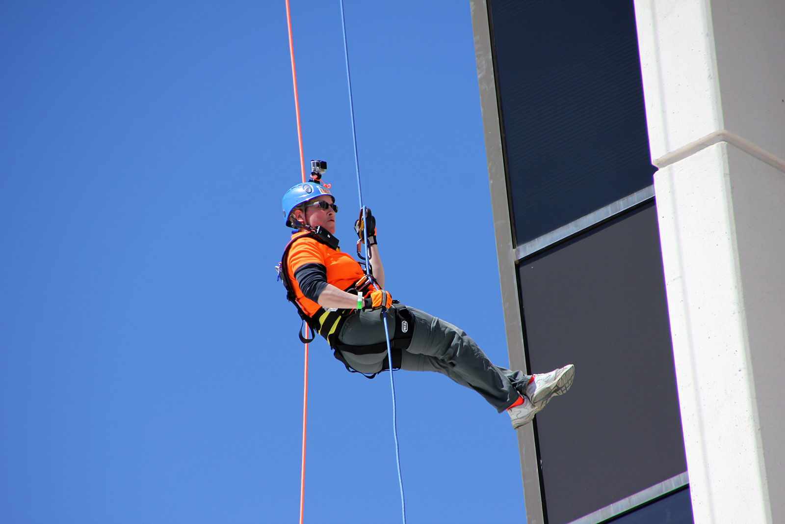 Worker on a rope repelling down a building