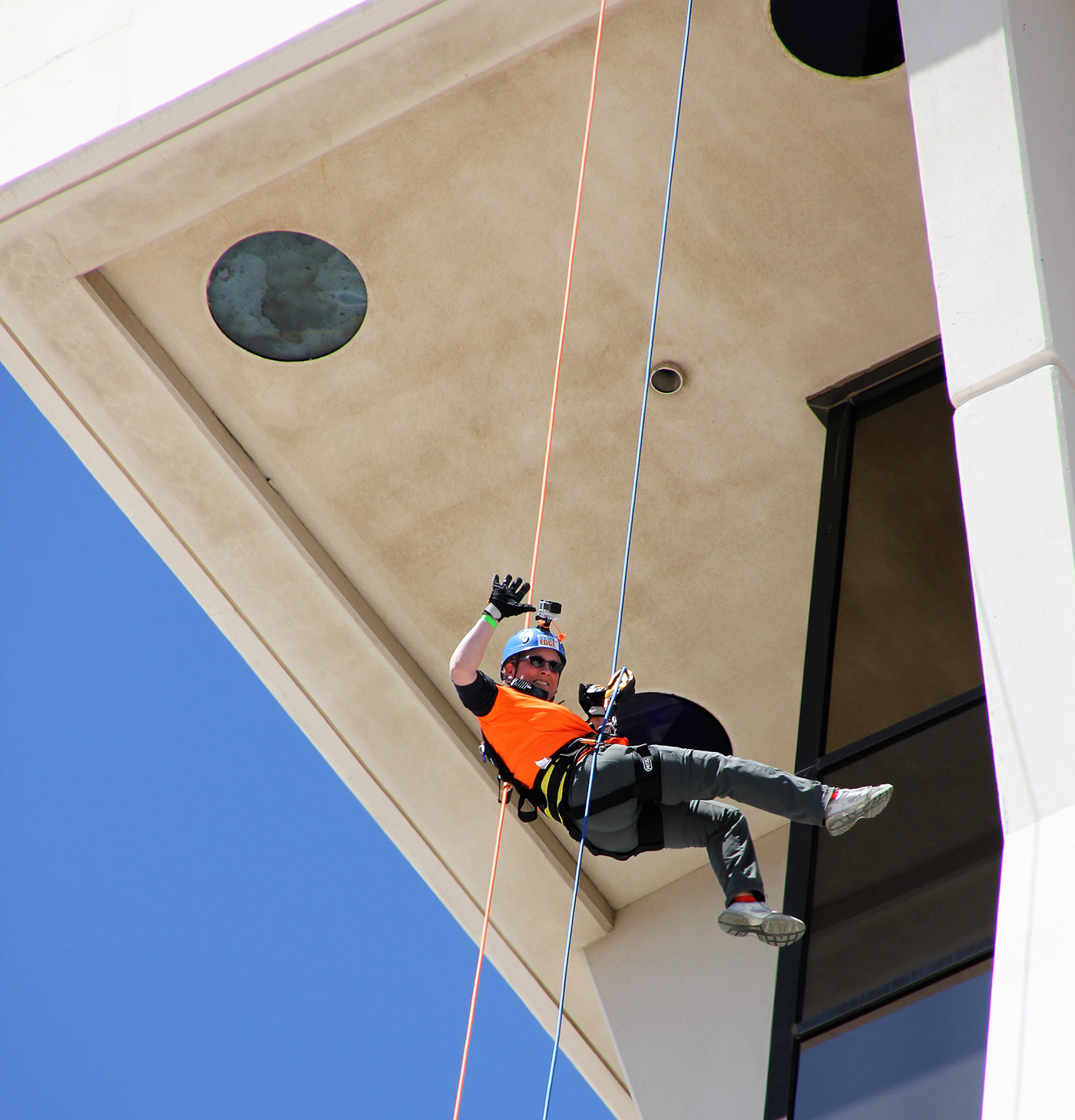 Underside of a building with a worker repelling down