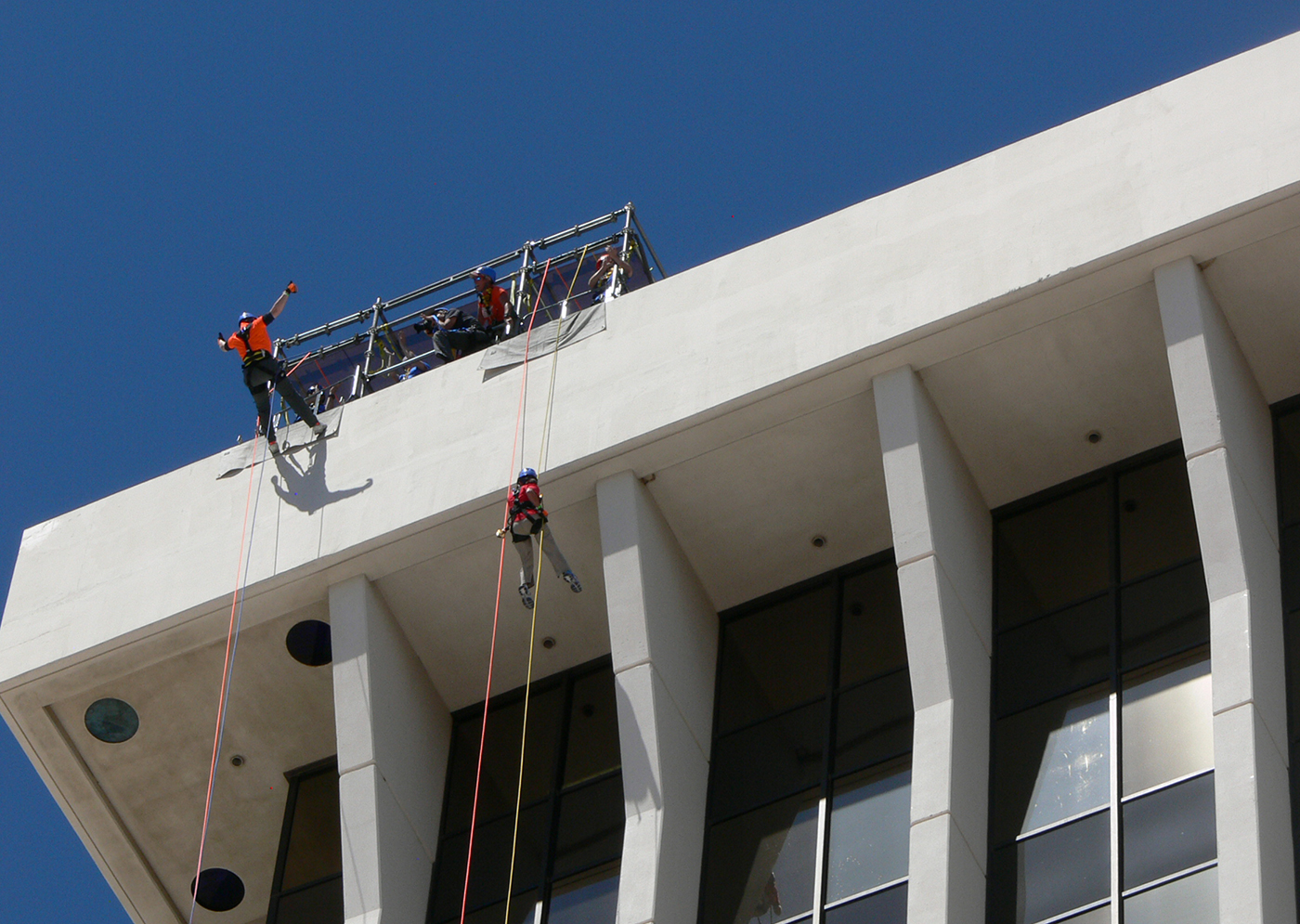 Worker starting to repel from the top of the building