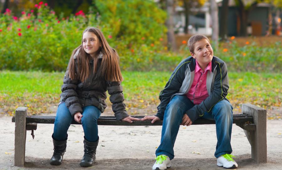 niño y niña tímidos en el banco del parque