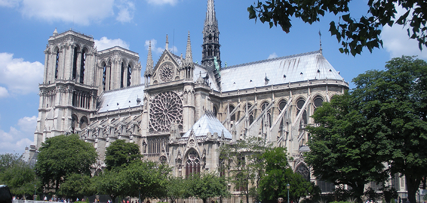 The Notre-Dame de Paris on a sunny day, surrounding by green trees