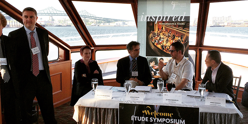 Attendees at an Encore Tours Etude Symposium in formal attire, standing and sitting around a table with a white tablecloth and wine glasses on top of it; Boston Harbor visible through the large windows of the ship in the background