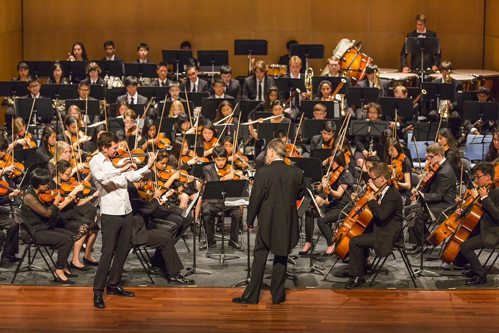 Orchestra performing in concert hall setting