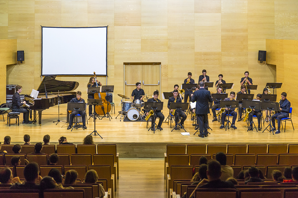 Band performing in concert hall setting in front of audience