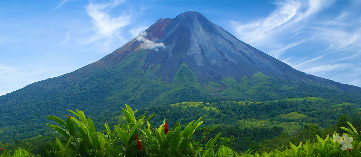 The majestic Arenal Volcano towering high into the blue sky above the swirling clouds about its summit, covered in trees at its base