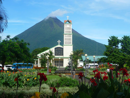 Colorful Costa Rican flora in front of the small but charming church, Iglesia de La Fortuna de San Carlos, located at the base of the Arenal Volcano
