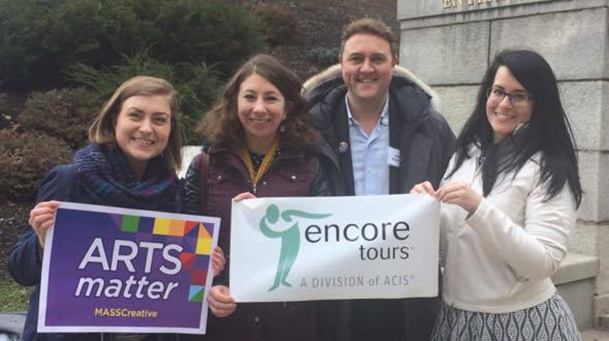 "Four people standing in front of the Massachusetts State House holding signs that read ""Arts Matter!"" and ""Encore Tours"""