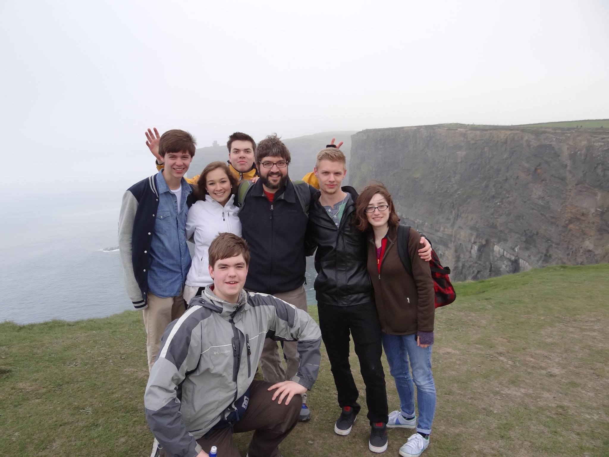 Nathan Cohen and his students posing for a group photo atop the Cliffs of Moher on a foggy day