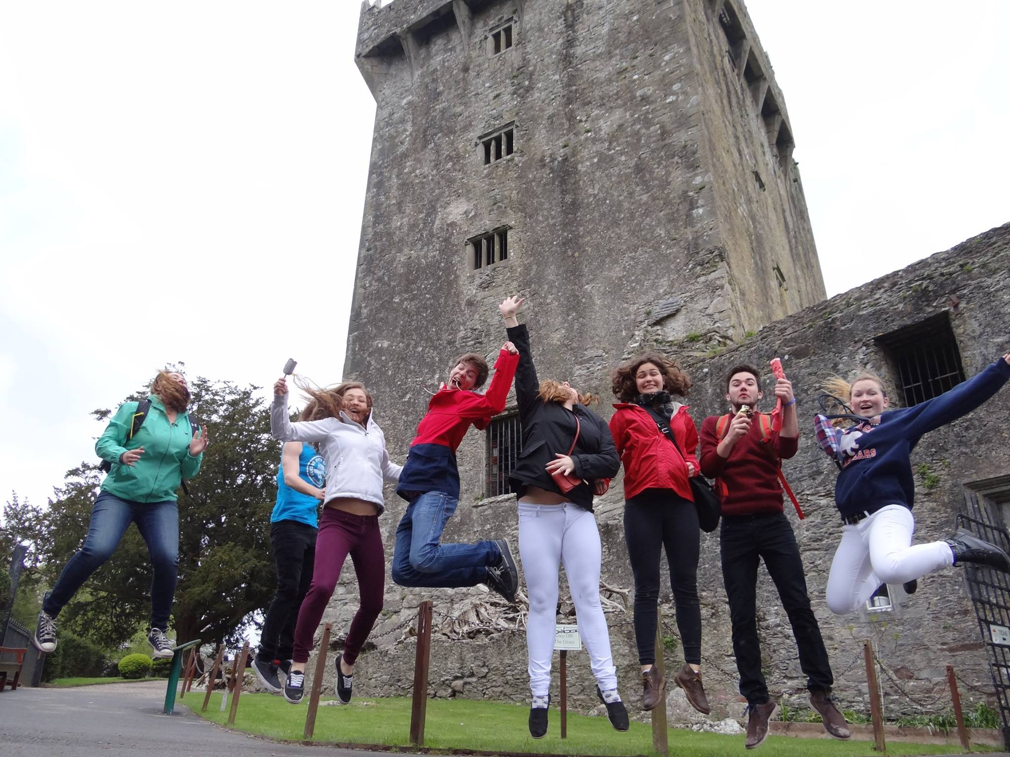 The 2014 Rockport High School Orchestra tour students jumping in the air outside of Blarney Castle in Cork