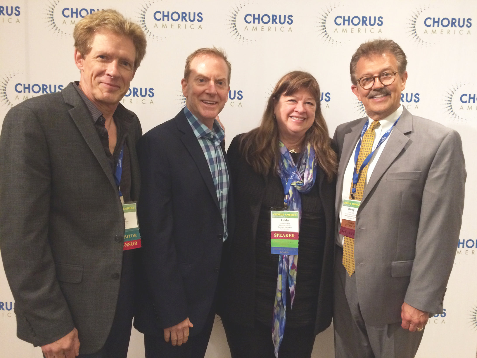 Four music directors in formal attire, including Encore's Ward Dilmore, smiling for a group photo at Chorus America with name tags and white Chorus America logo-covered backdrop