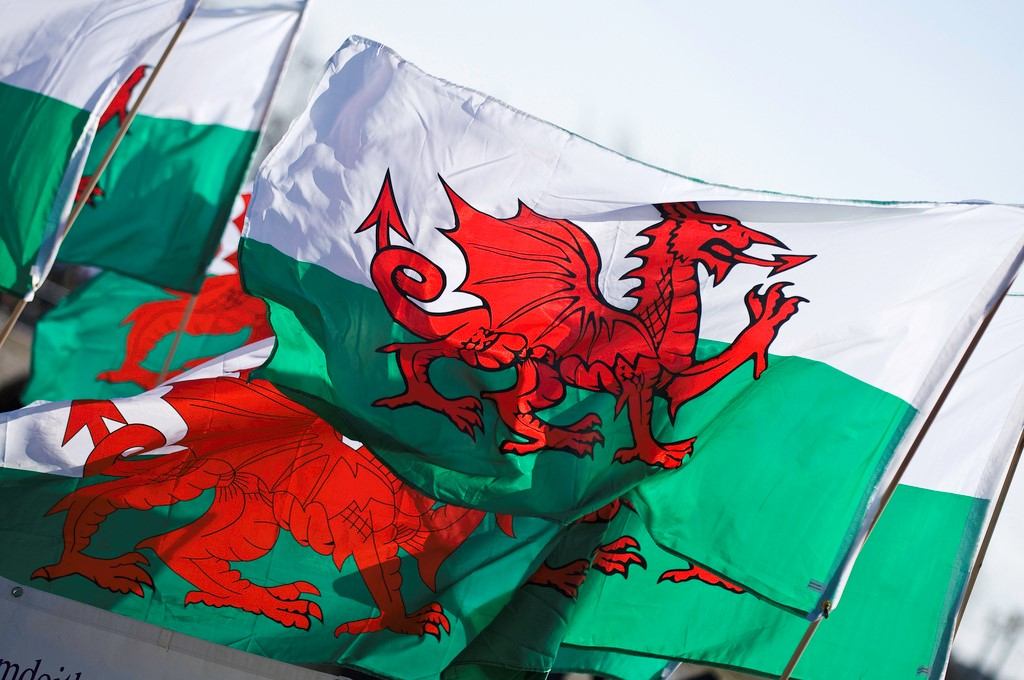 An image of the Welsh flag. The flag is white and green with a red dragon at its center.