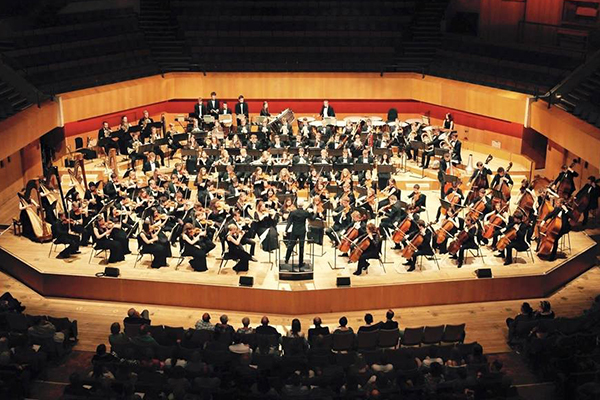 An image of the National Youth Orchestra Wales performing on a stage. Performers are dressed in black concert dress.