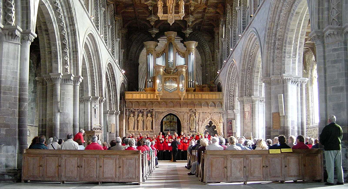 An image of the inside of a Welsh cathedral. A choir dressed in red robes is singing at the front of the cathedral and audience members are watching the performance.
