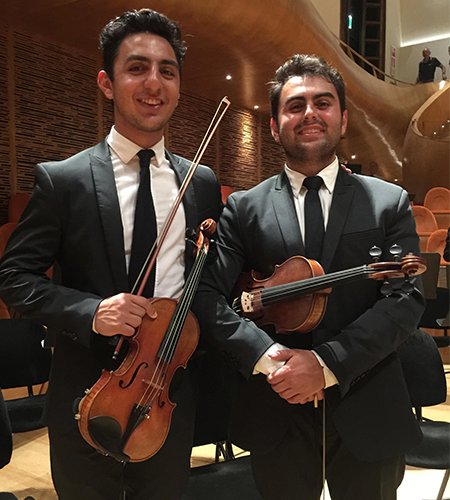 Two young people in tuxes with violins in a concert hall.