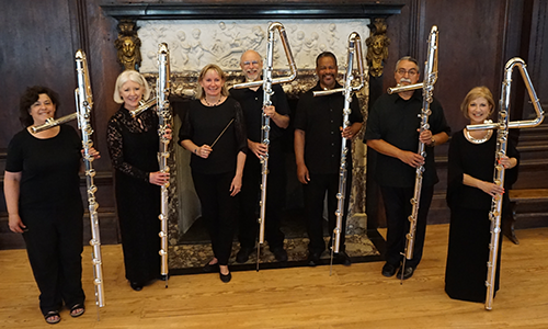Paige Long and the Metropolitan Flute Orchestra standing in front of an ornate fireplace, wearing formal attire, and holding their flutes, which are as tall as them (or even taller than!).
