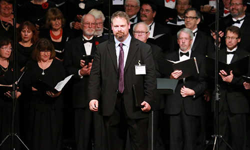 Sean Boulware and the California Coast Chorale standing on stage wearing formal attire, facing the audience and preparing to perform