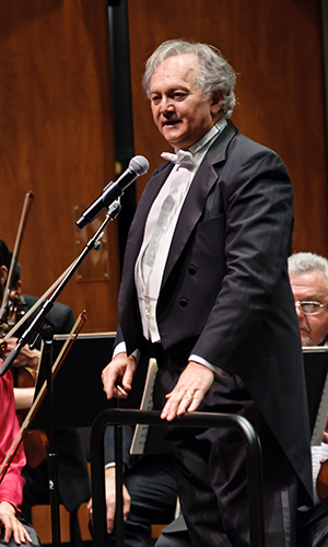 Michael Neumann wearing a tuxedo and speaking into a microphone on stage in a concert hall, with the Sacramento Youth Symphony seated behind him