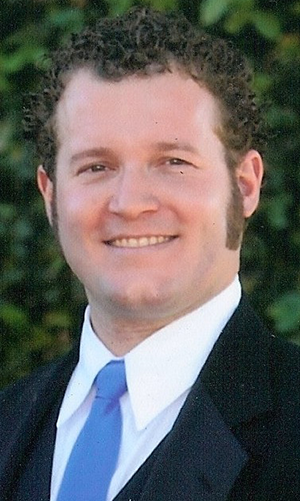 Professional portrait of Drake York wearing a tuxedo and a blue neck tie, standing in front of foliage