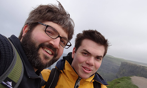 Nathan Cohen taking a selfie with a student at the Cliffs of Dover on a foggy day